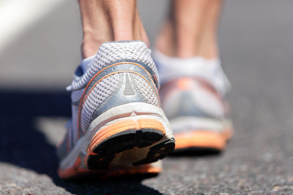 Running shoe closeup of man running on road with sports shoes. Road to success. Runner training cardio exercising, walking or start of run on marathon race road. Feet health, heel care.